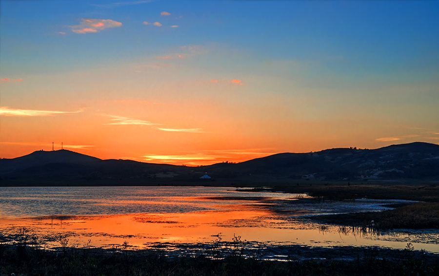 夕阳已完全沉入地平线,金红色的晚霞渐渐染红了天空